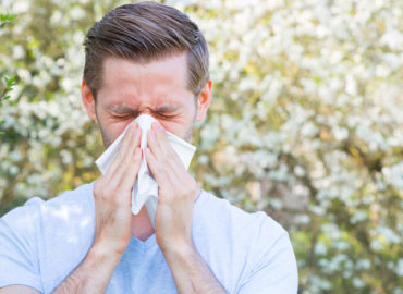 Man with allergies aggressively blowing into a tissue