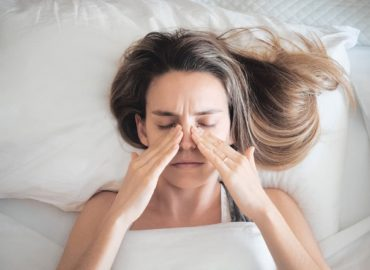 Woman lying in bed, rubbing her blocked sinuses caused by allergies