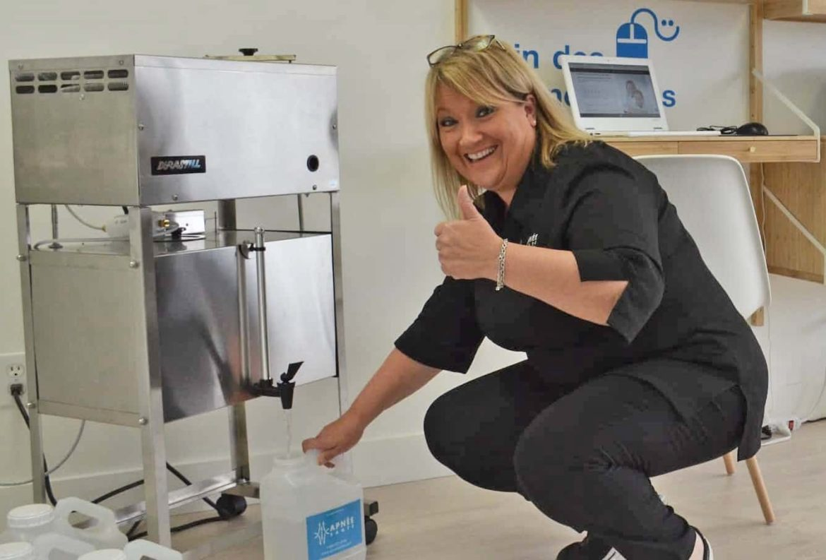 An Apnée employee refilling a bottle of distilled water from a machine in the office