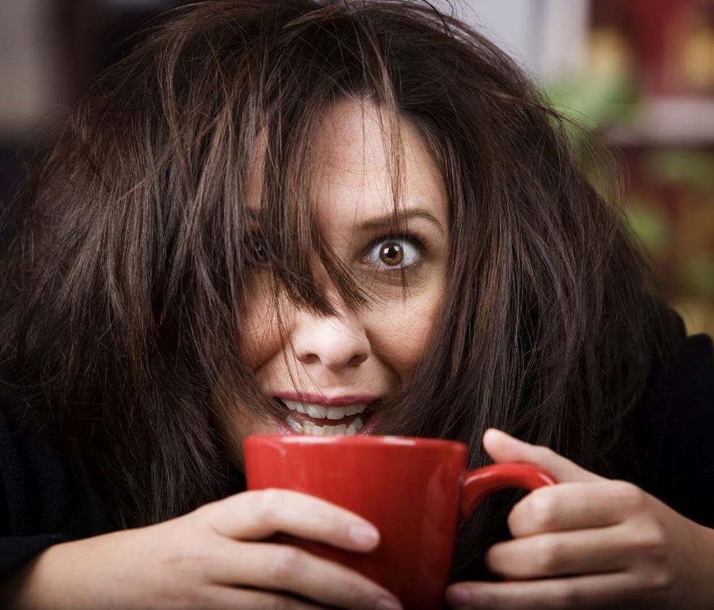 heavily caffeinated woman tightly holding a cup of coffee