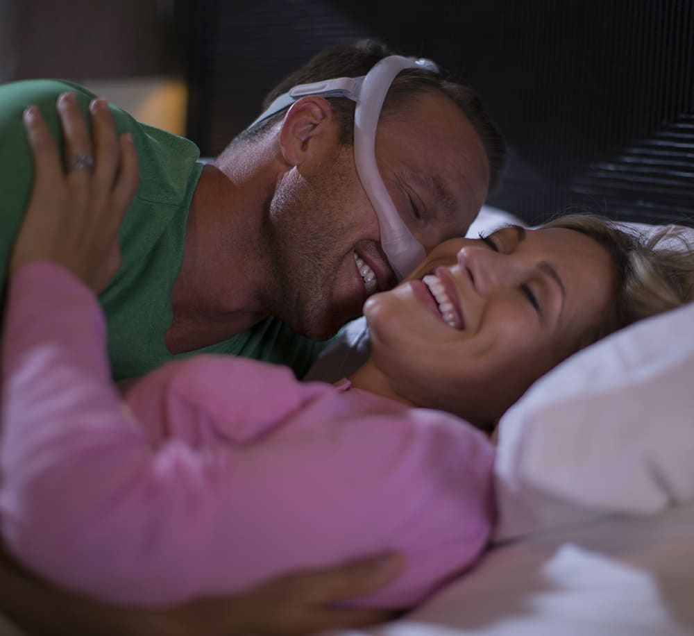 man wearing cpap mask cuddles his wife in bed