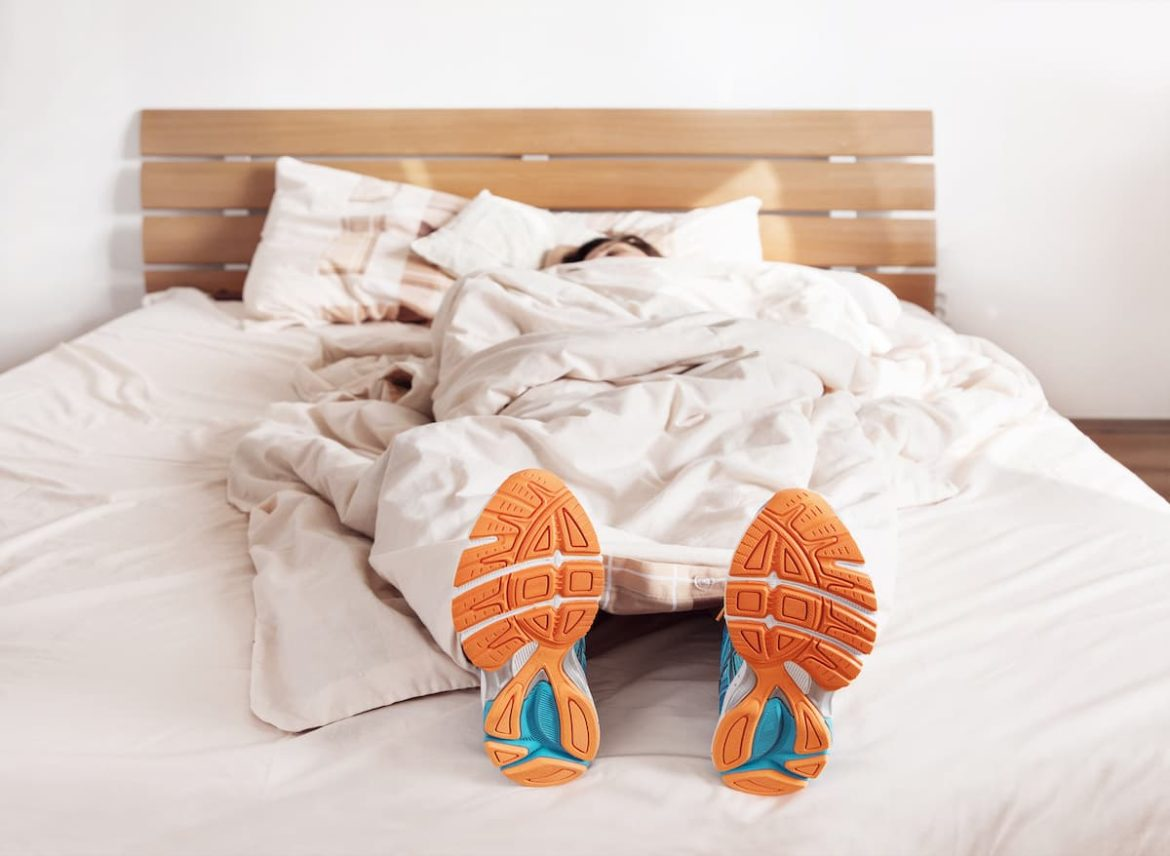Person sleeping in bed with exercise shoes on