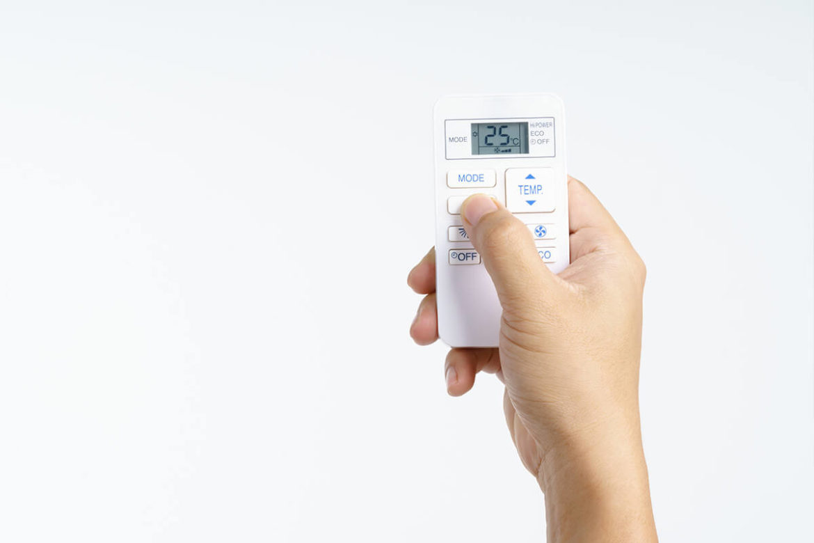 Hand holding up an air conditioner remote control