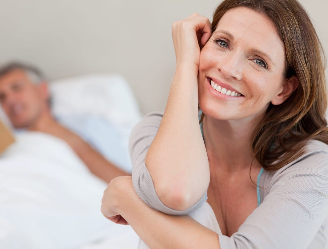 Happy well rested woman with sleeping husband in background