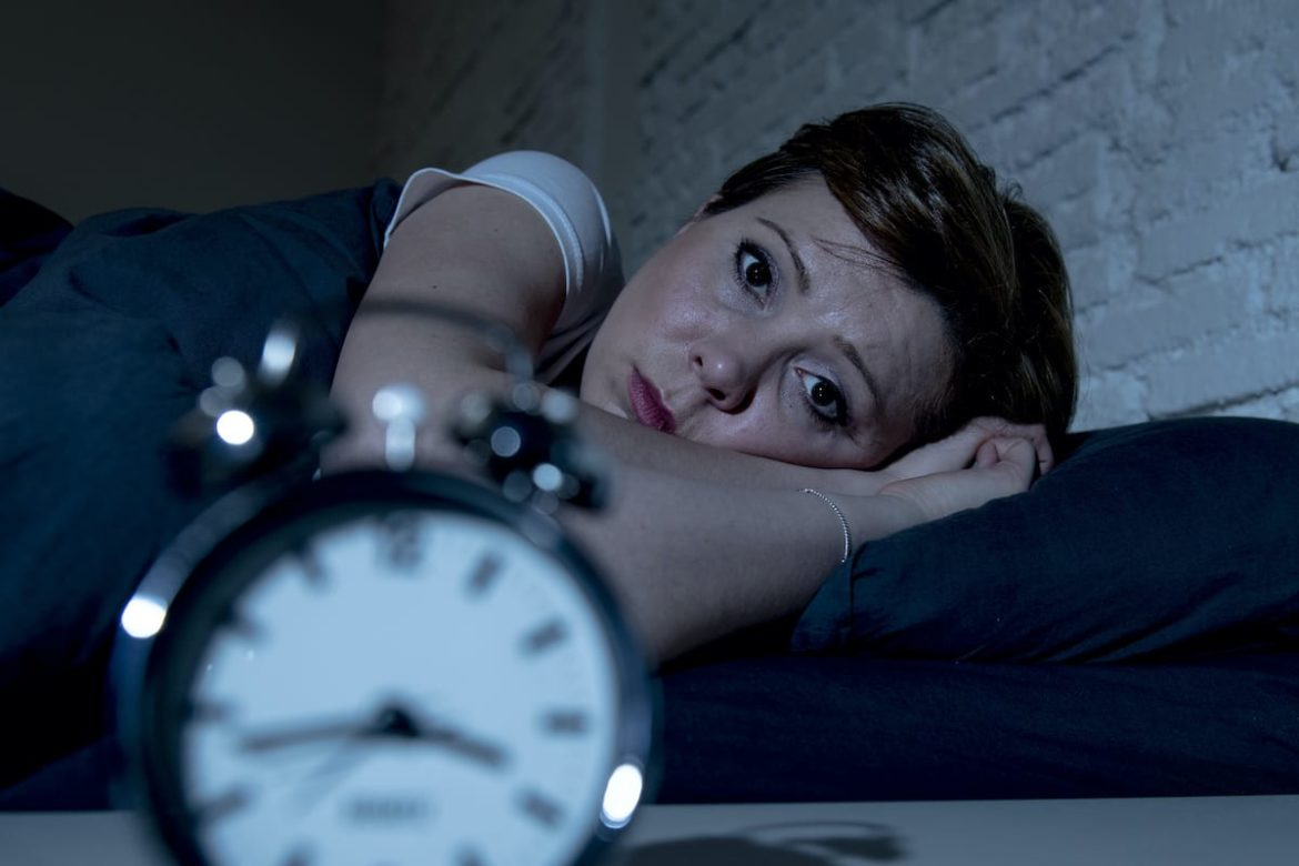 Worried Woman lies in bed at night, staring at the clock