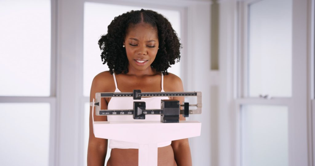 Woman unhappily looks at her weight while standing on a scale