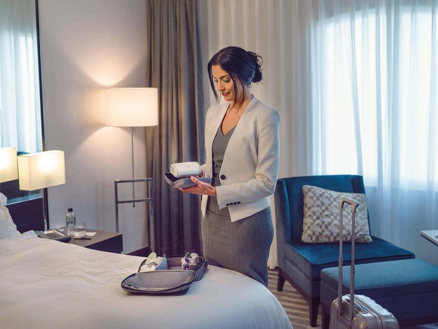 Thirty-something, professional woman in a hotel room putting her Resmed AirMini portable CPAP machine in a carry-on suitcase