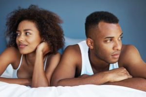 Man and woman sit in bed looking uncomfortable