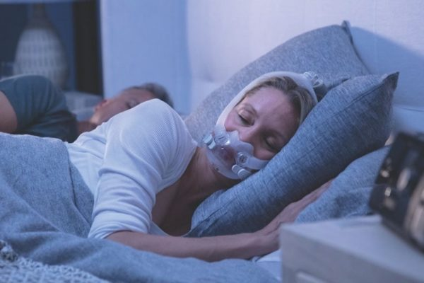 Woman sleeping in bed with CPAP mask