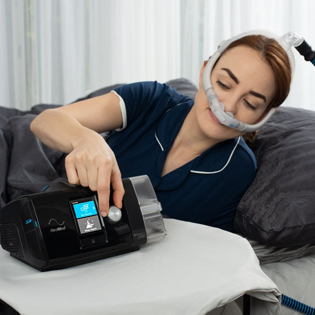 woman adjusts settings on her CPAP machine