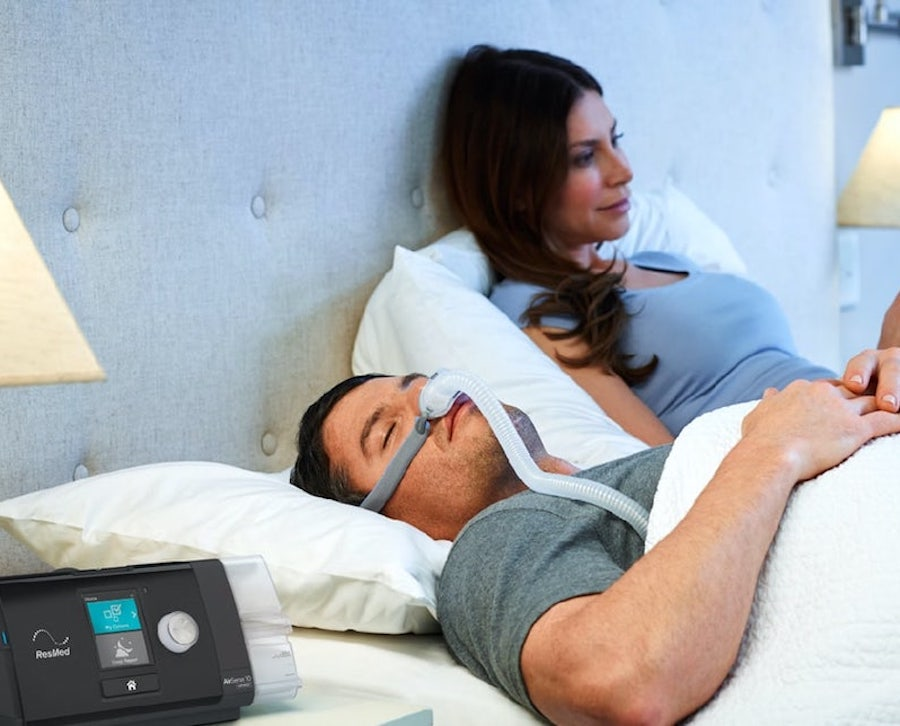 Man sleeping in bed while wearing an AirFit P10 CPAP mask