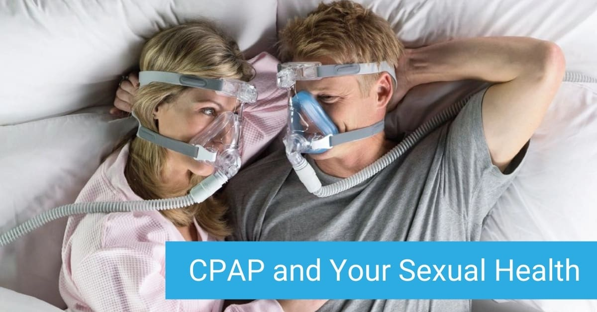 cpap and your sexual health - Smiling man with CPAP mask on, lies next to partner in bed, also wearing a CPAP mask