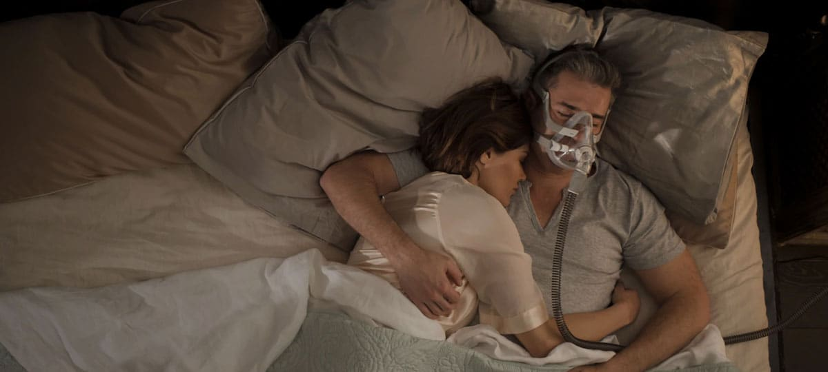 man wearing an AirFit F20 mask in bed