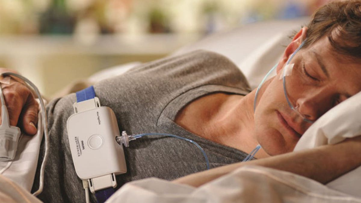 Man in bed asleep with a monitor around his chest