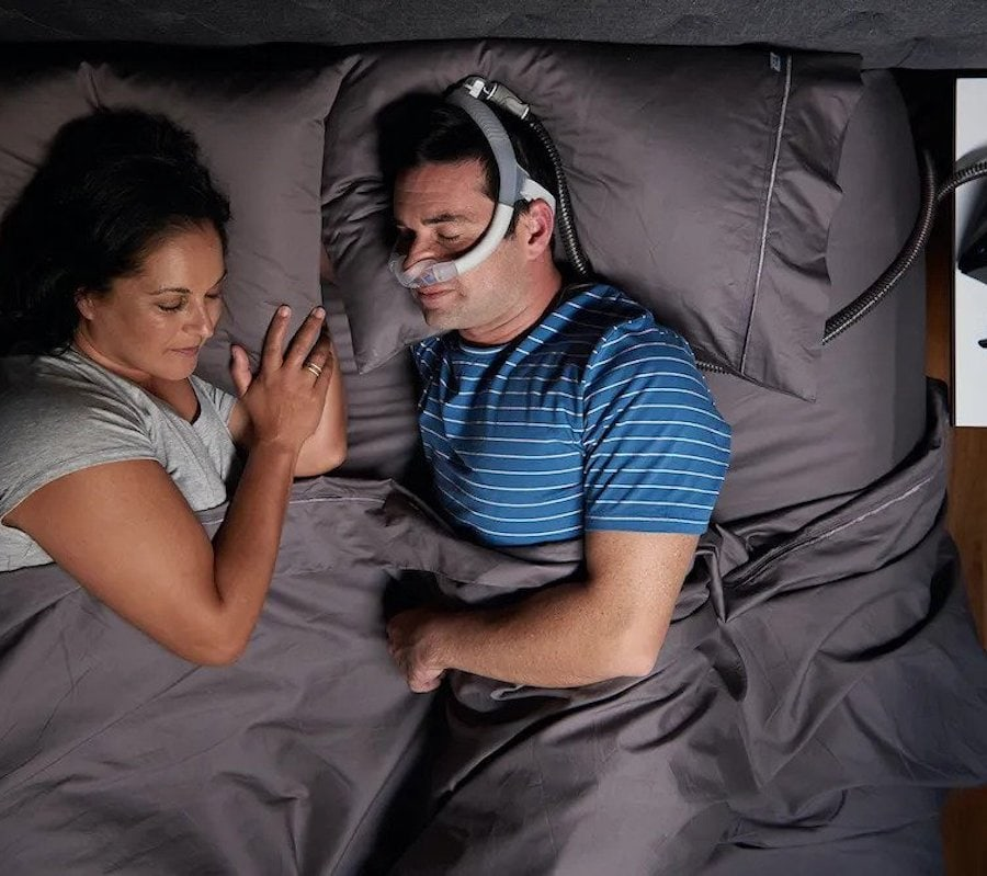 Man sleeping comfortably in bed, wearing a CPAP nasal pillow mask
