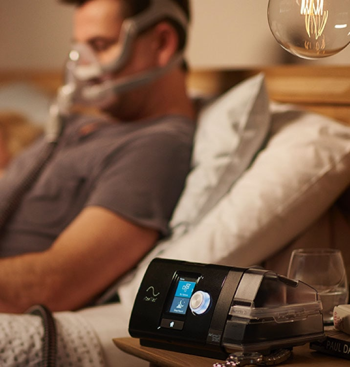 man sitting in bed, next to his Airsense 10