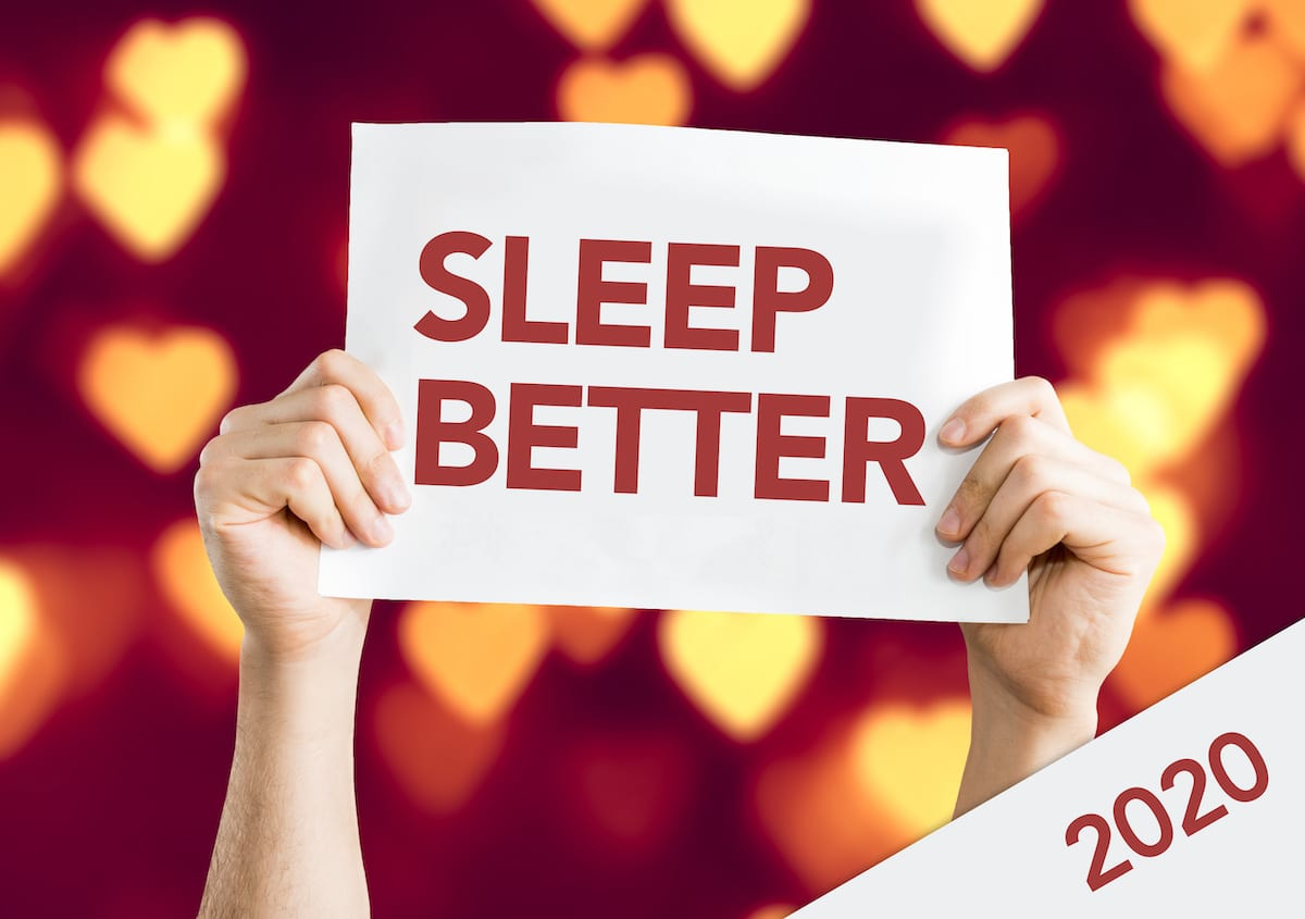 Man Hand Holding Paper containing the red text Sleep Better. Isolated on festive New Year background with white lights. Caption in bottom left corner with text 2020.