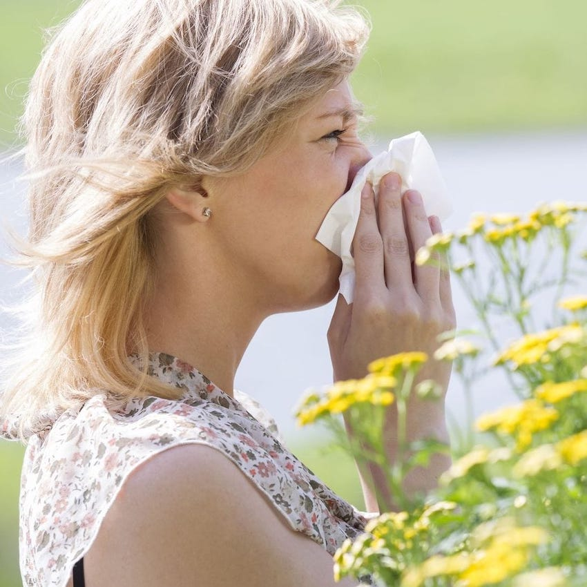 woman next to flowers, blowing her nose