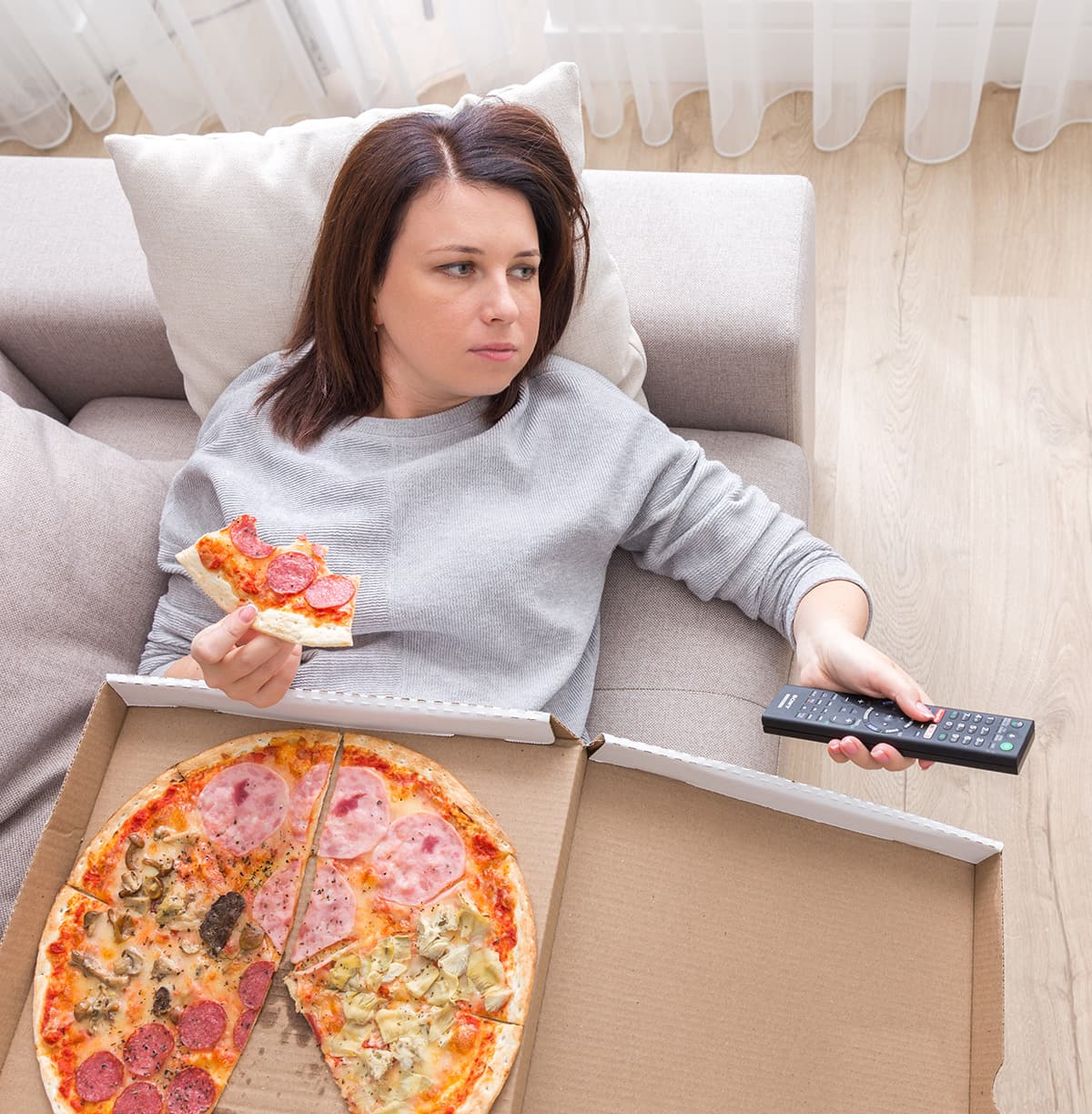 tired woman eating pizza on couch
