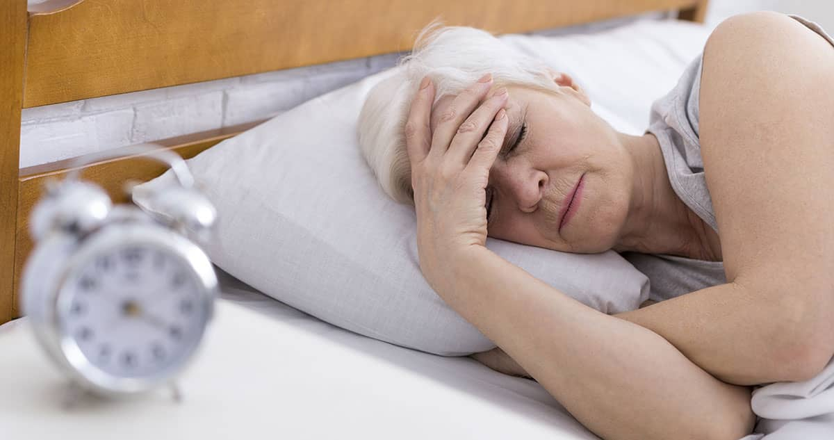 50 year old woman, suffering from apnea and menopause lying in bed sleepless with hand on head